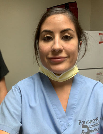 Profile view of Alvarado wearing scrubs with her mask pulled down to smile