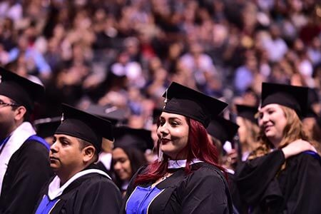 focus on female student in crowd surrounded by classmates at graduation