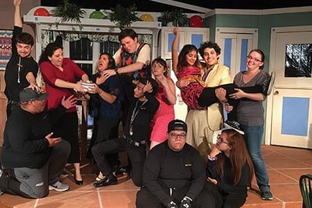 A group of theatre students posing in silly ways with the set behind them