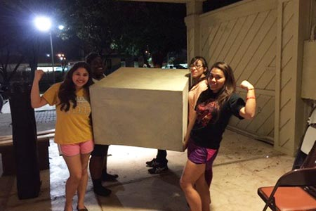Four theatre tech students carrying a large box and showing off their muscles