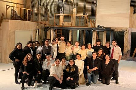 A group of theatre students posing on stage with a half-built set behind them