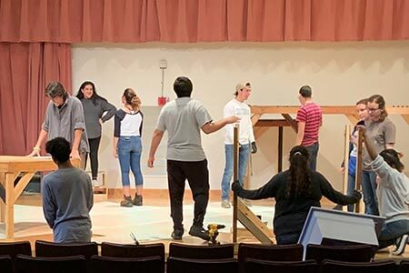 A group of theatre tech students assembling wooden sets on stage