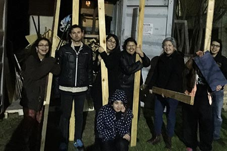 A group of theatre tech students holding wooden set pieces and smiling