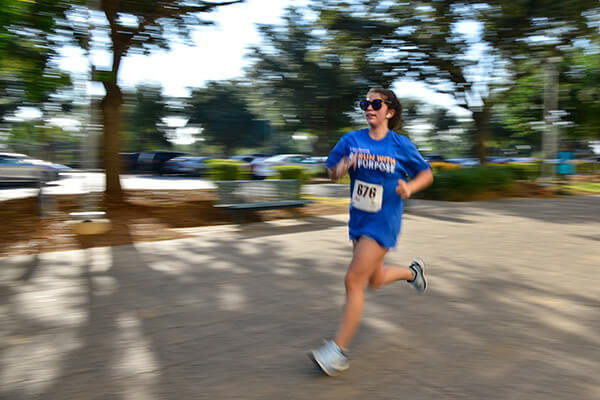 Woman runs in St. Mary's shirt.