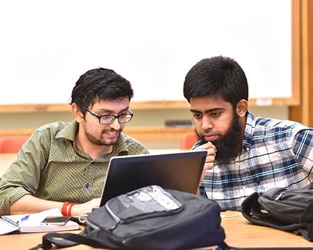 two male cybersecurity students working on laptop