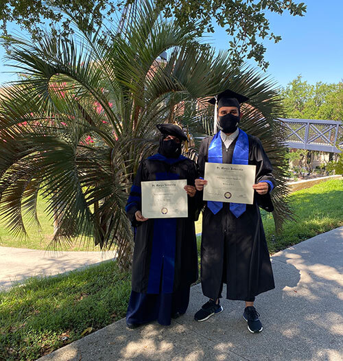 International graduates Reema Alhowaish and Abdul Almaghlooth pose on campus with their degrees.