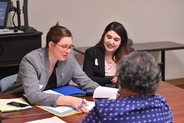Two law students help a client.