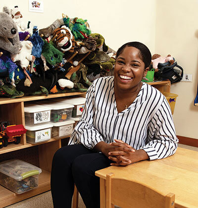 counseling student sits at a child-sized table surrounded by toys and stuffed animals