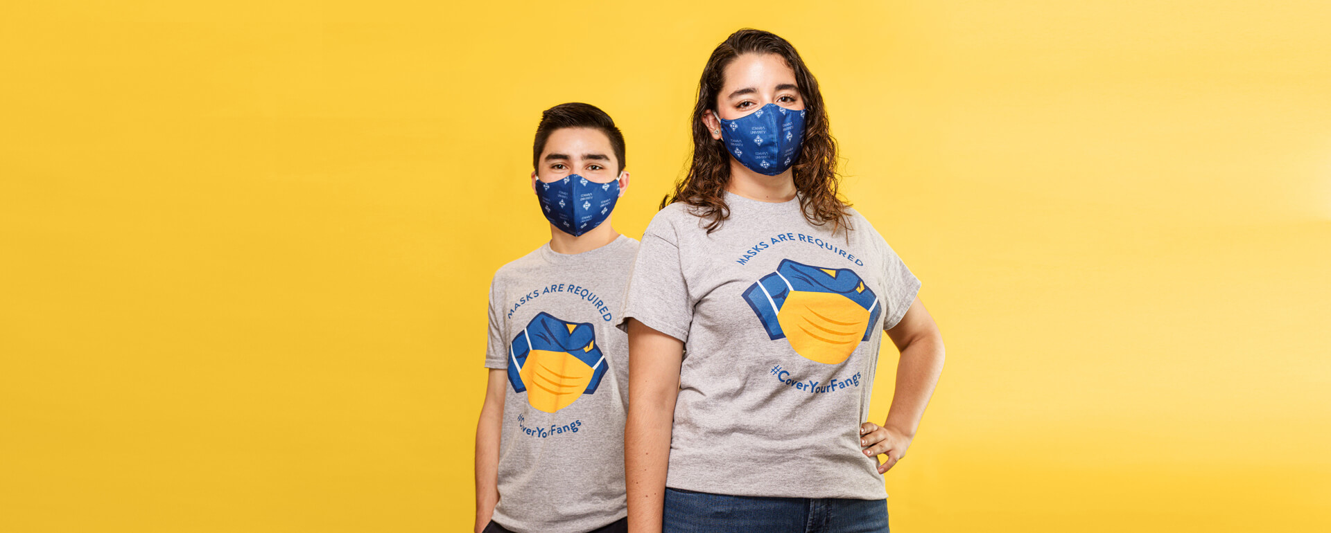 two students in Mask Squad t-shirts and St. Mary's branded masks with a yellow background