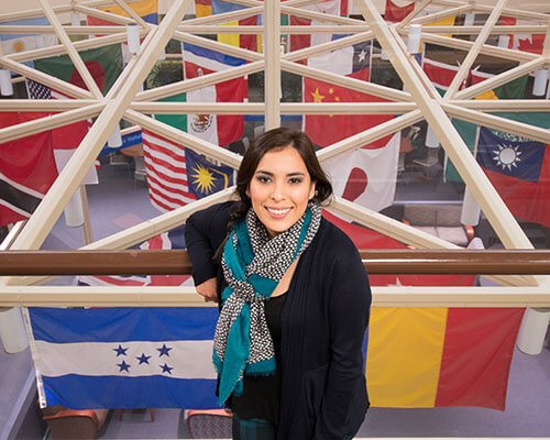 student in front of many international flags