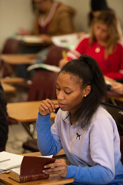 A female student reading a Bible in class.