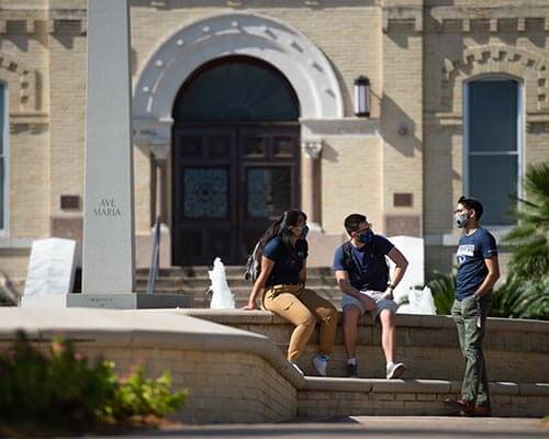 three students with face masks sit in front of St. Louis hall