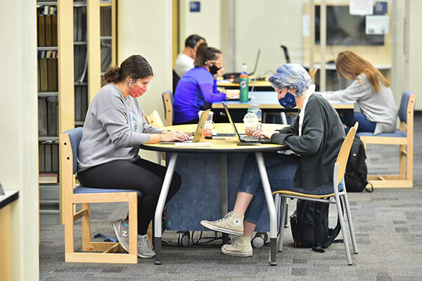Students studying together in the Commons, wearing facemasks.