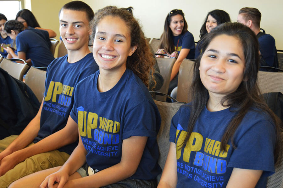 Three students smiling while wearing Upward Bound t-shirts