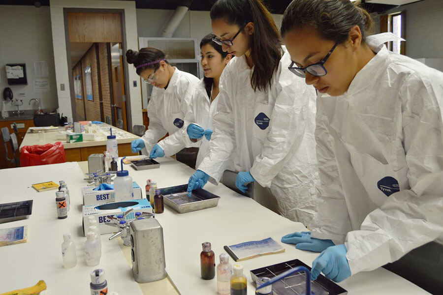 Four students in lab coats working in a laboratory