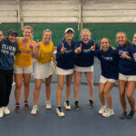The Rattler Women's Tennis team celebrates their win on court.