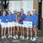 Six women in their golf uniforms hold the winning trophy.