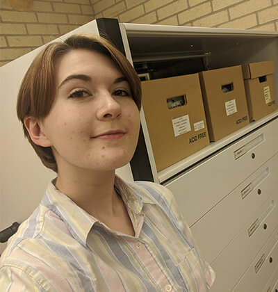 Public History student Glory Turnbull in an archives featured