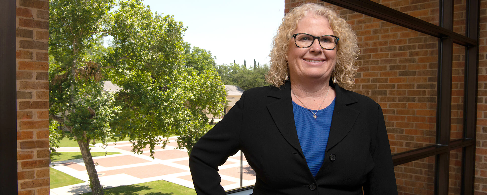 Stephanie Ward stands on an balcony overlooking Alkek Plaza.